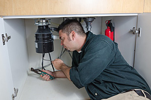 Paul is under the sink working on a garbage disposal repair in Ellicott City
